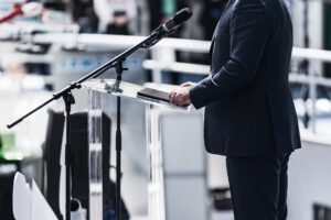 Male Speaker Standing In Front Of Microphones